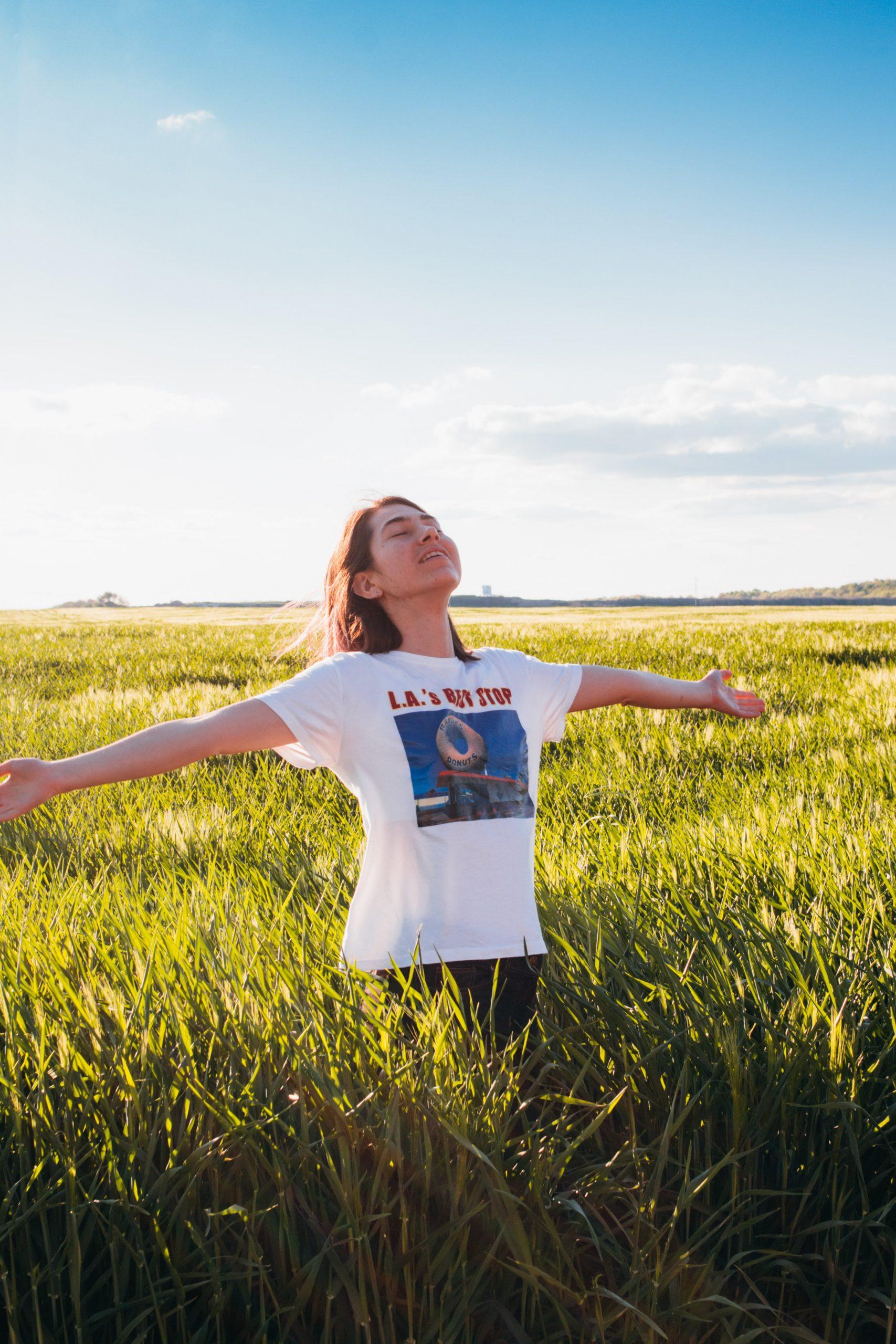 mulher no campo com braços abertos